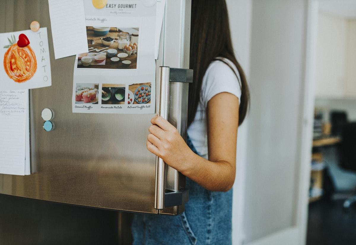 Frau schaut in einen geöffneten Kühlschrank, sie ist von der Seite zu sehen, ihr Gesicht hinter der Kühlrschranktür verborgen.