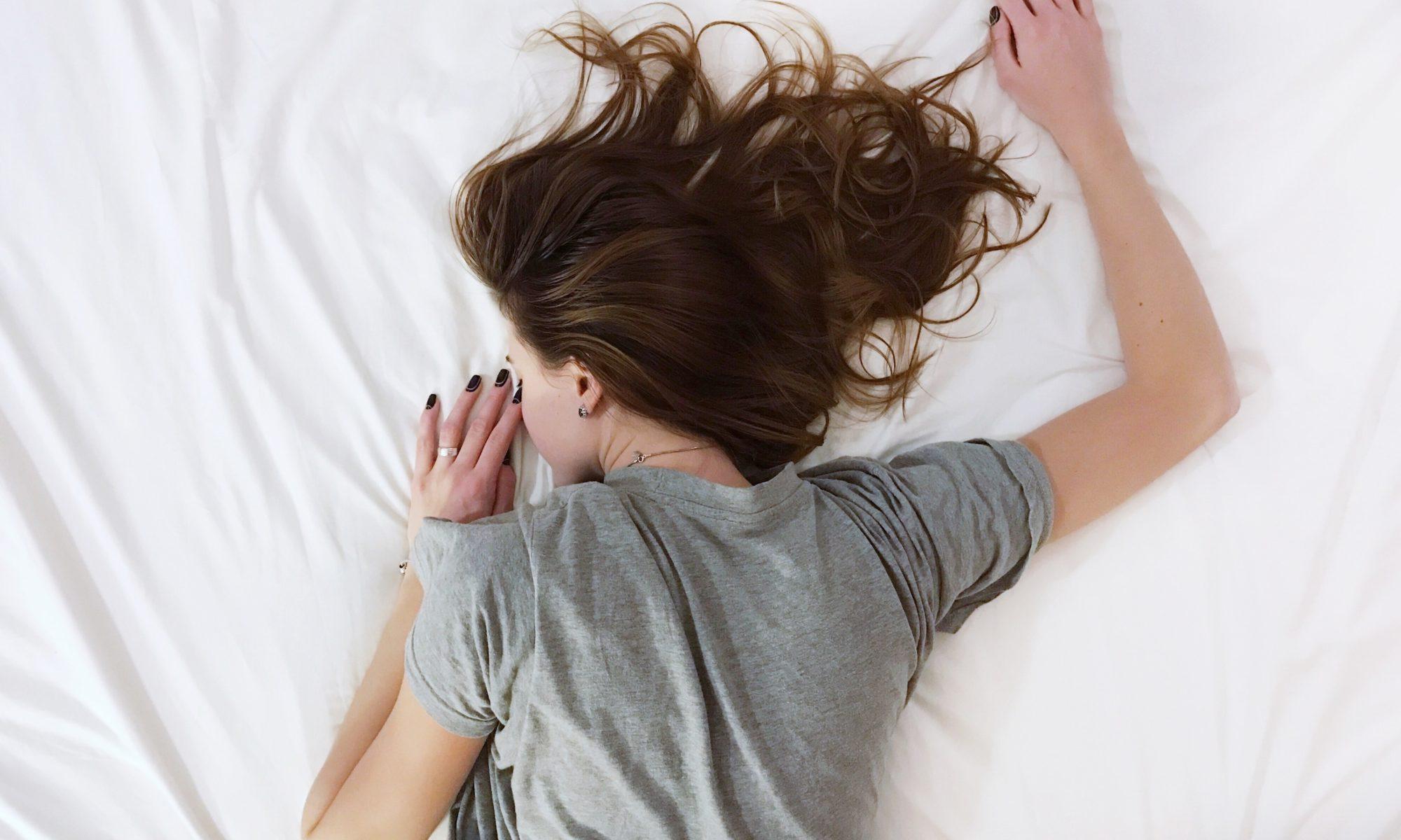 Frau liegt bäuchlings im Bett, zu sehen sind ihr Rücken und ihre langen Haare.