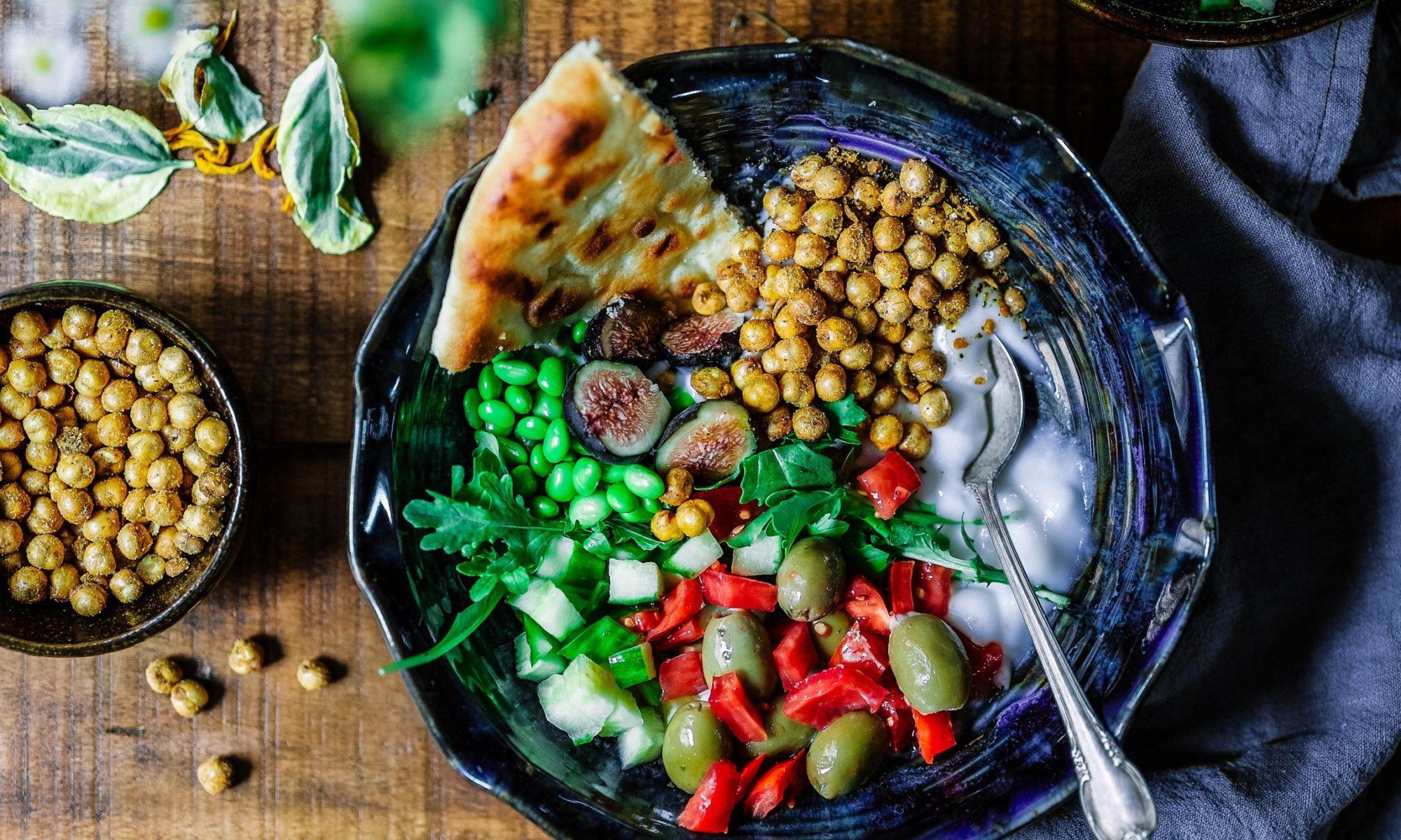 Salat aus Oliven, Gurken, Kichererbsen mit etwas Joghurt und einem Stück Fladenbrot in einer blauen Schüssel. die auf einer Holzoberfläche steht.