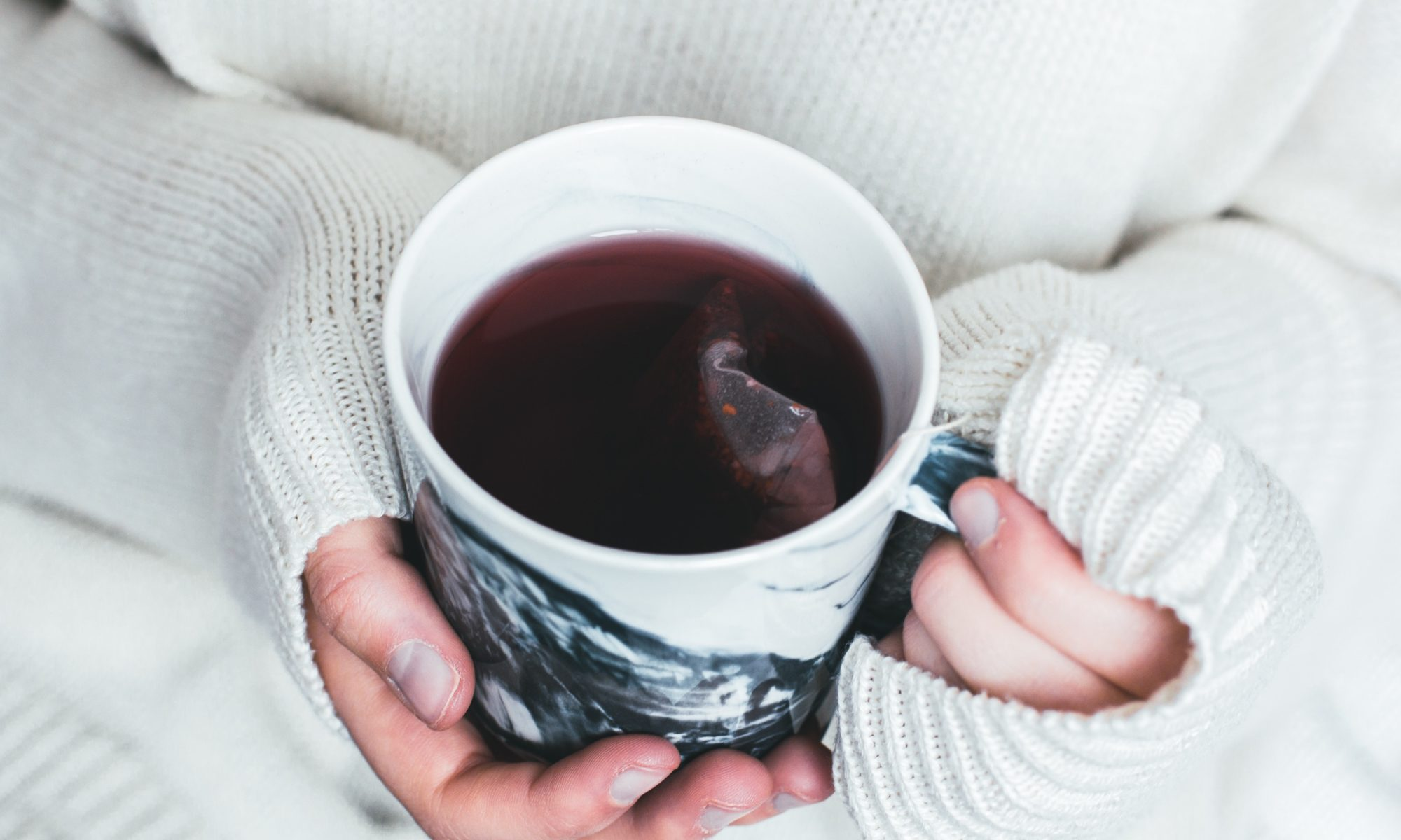 Hände, die eine Teetasse mit rötlichem Tee halten.