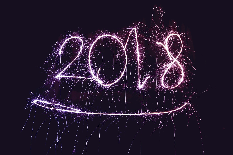 Lila-leuchtender 2018-Schriftzug vor schwarzem Hintergrund