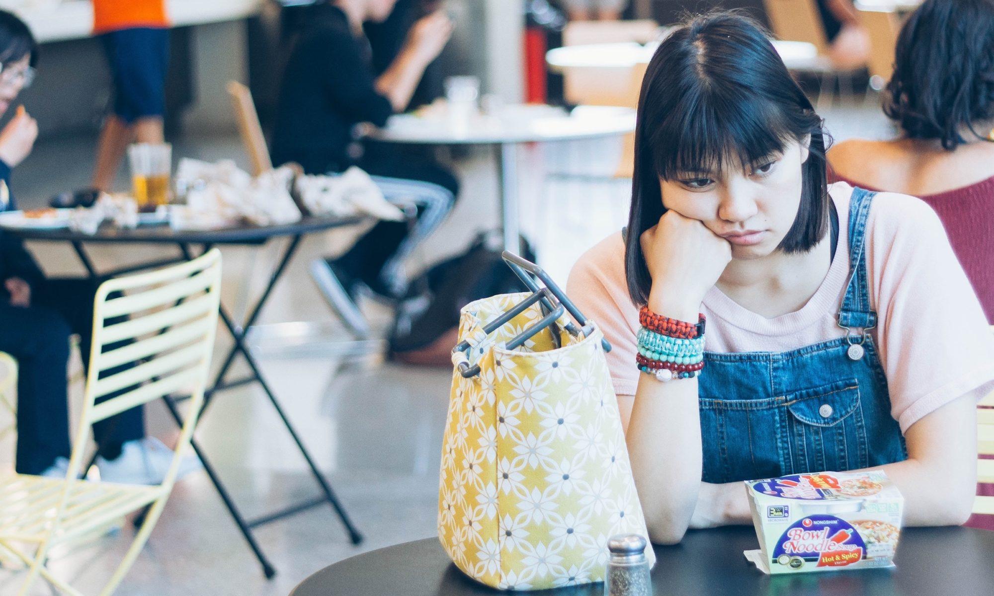 Frau sitzt mit traurigem Gesichtsausdruck in einem Café am Tisch.