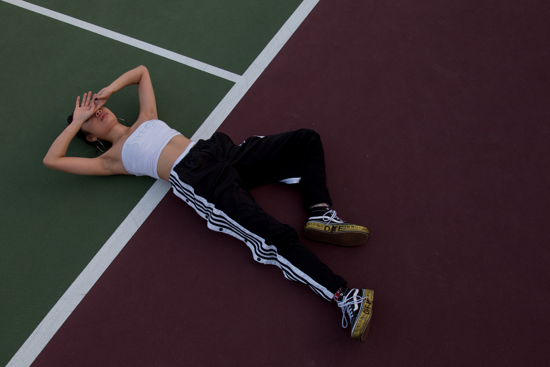 Eine Frau in sportlicher Kleidung liegt auf einem Sportplatz.