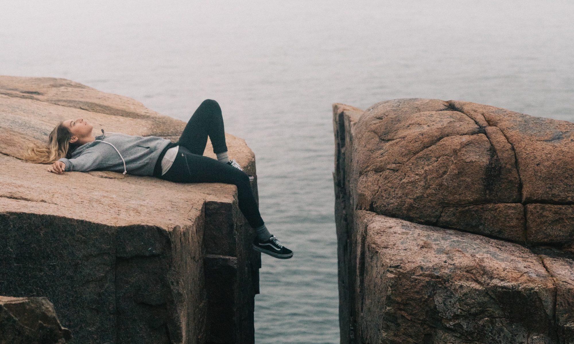 Bekleidete Frau liegt auf einem Felsen, im Hintergrund das Meer.