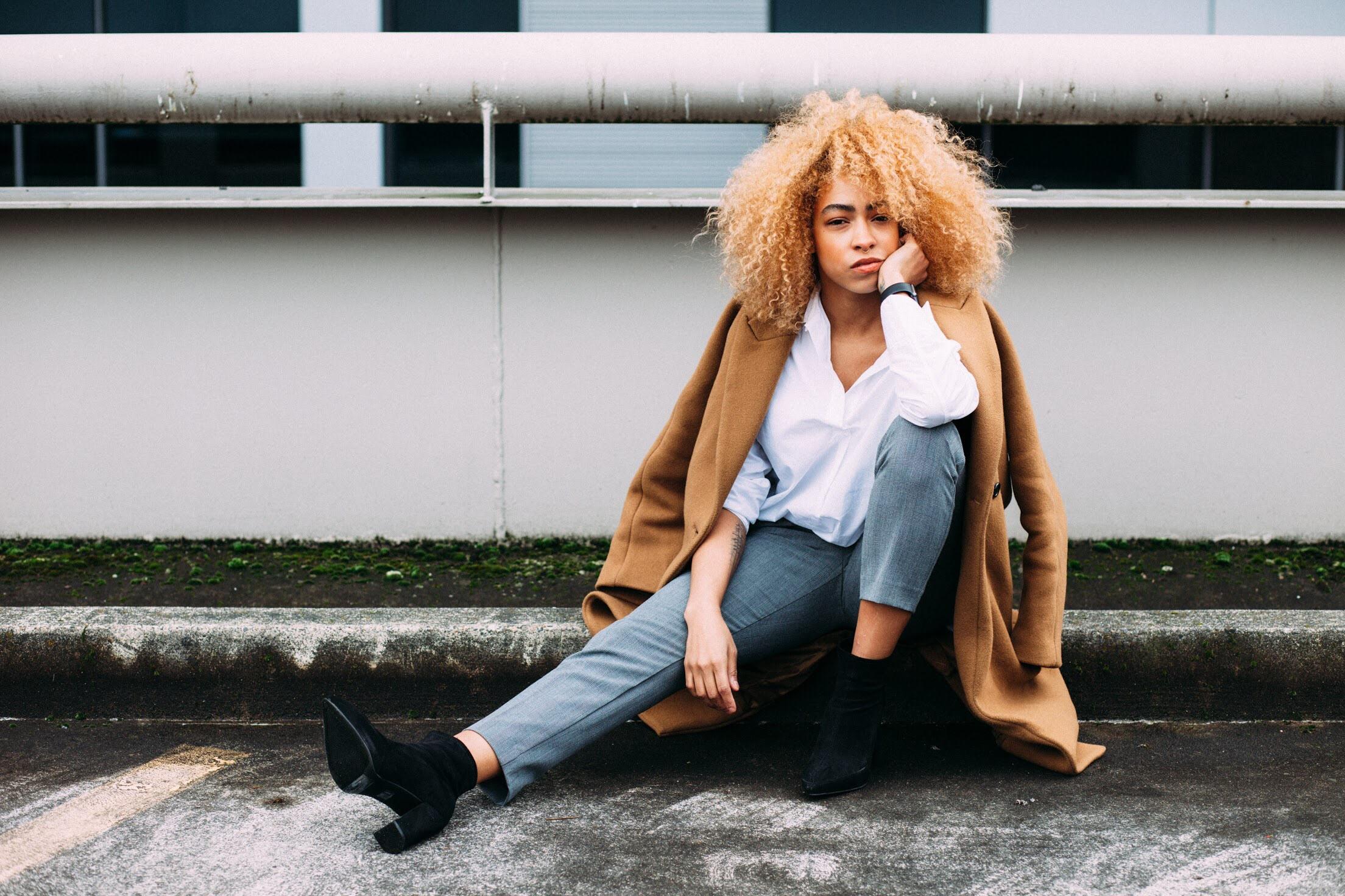 Entschlossen und leicht abweisend schauende Frau sitzt vor einem Gebäude, den Arm aufs Knie gestützt.
