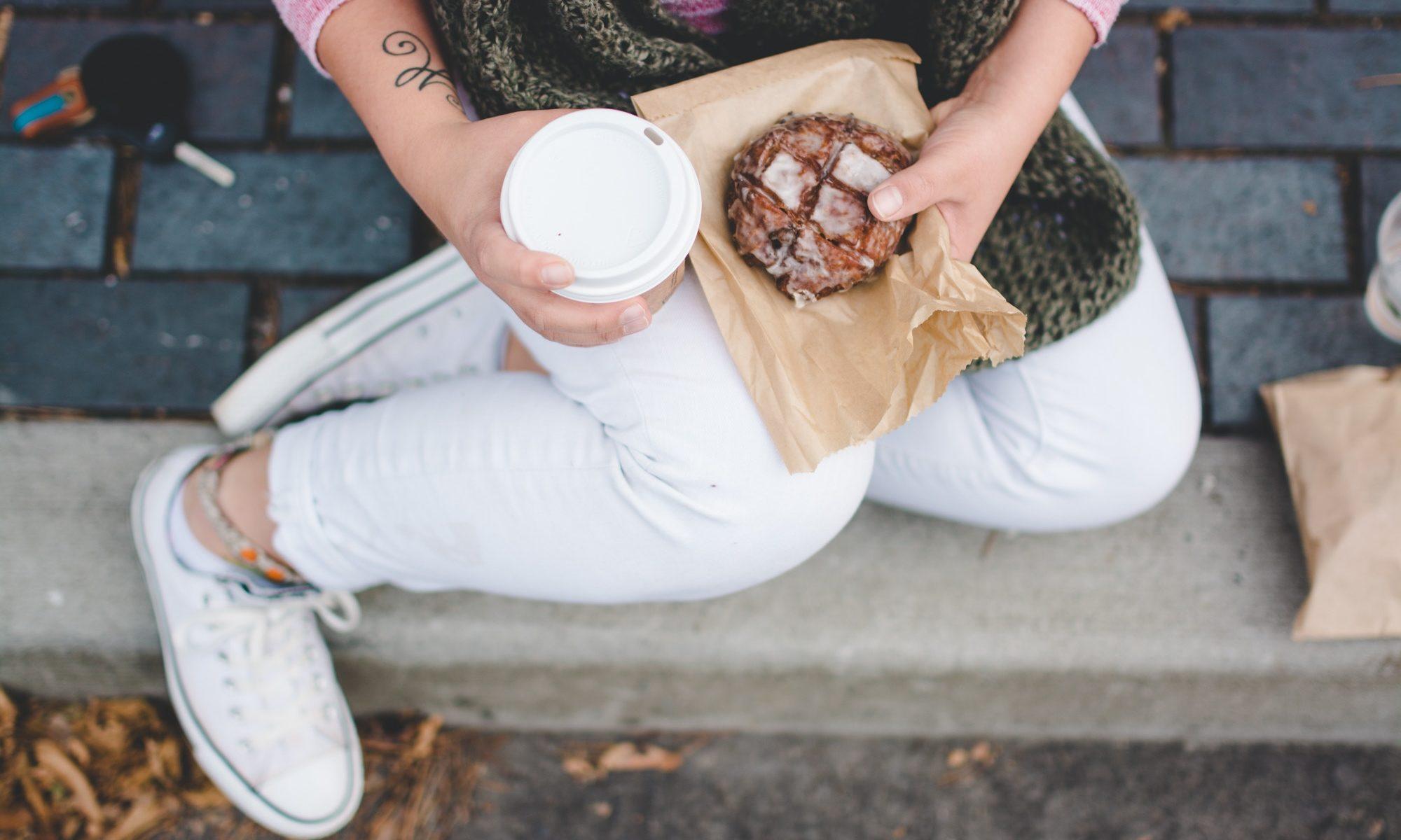 Draufsicht auf Beine einer Person, die einen Coffee-to-go-Becher und ein Gebäckstück in der Hand hält und auf der Straße sitzt.