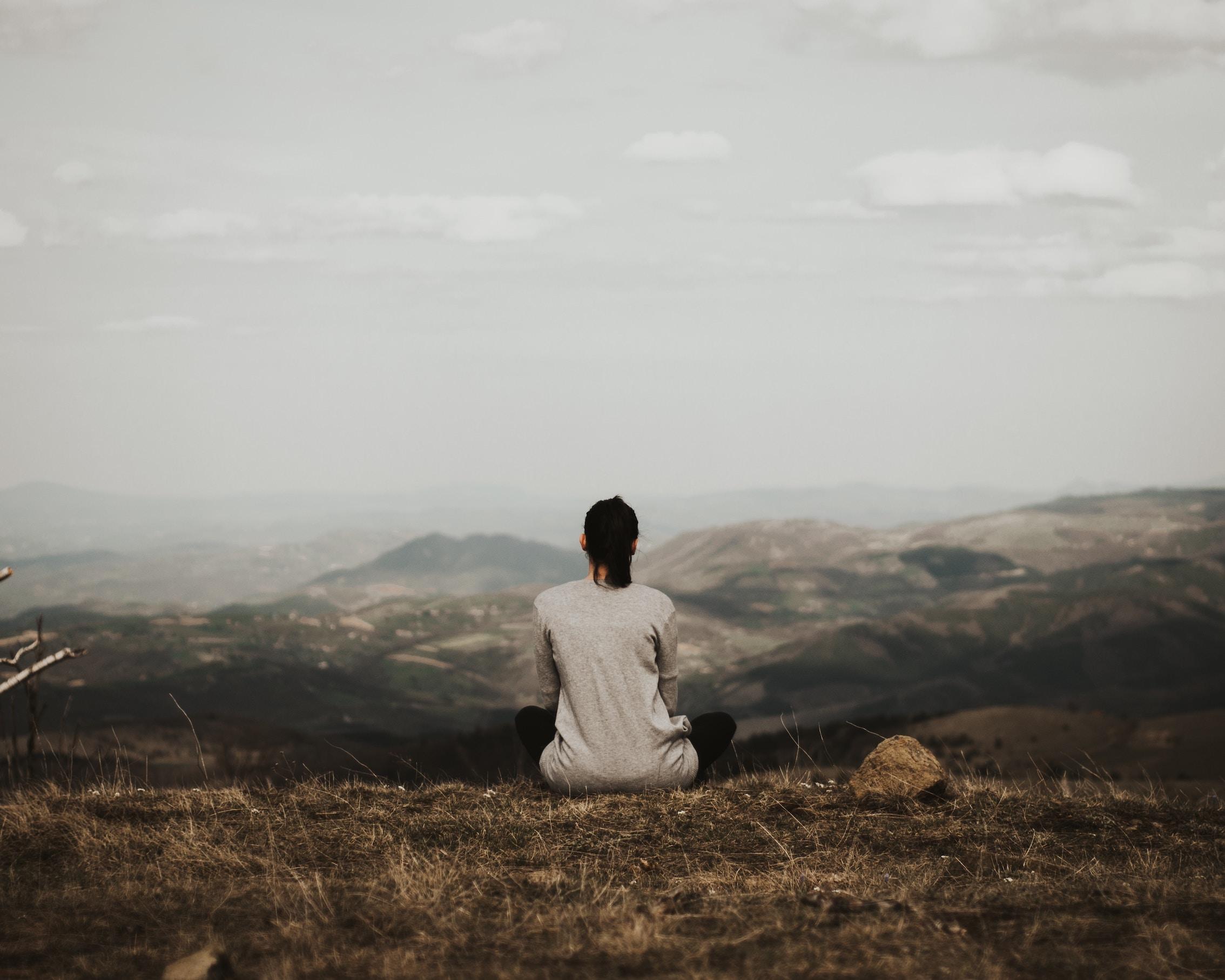 Blick auf einen Gebirgszug im Hintergrund, im Vordergrund die Rückansicht einer aufrecht sitzenden Frau.