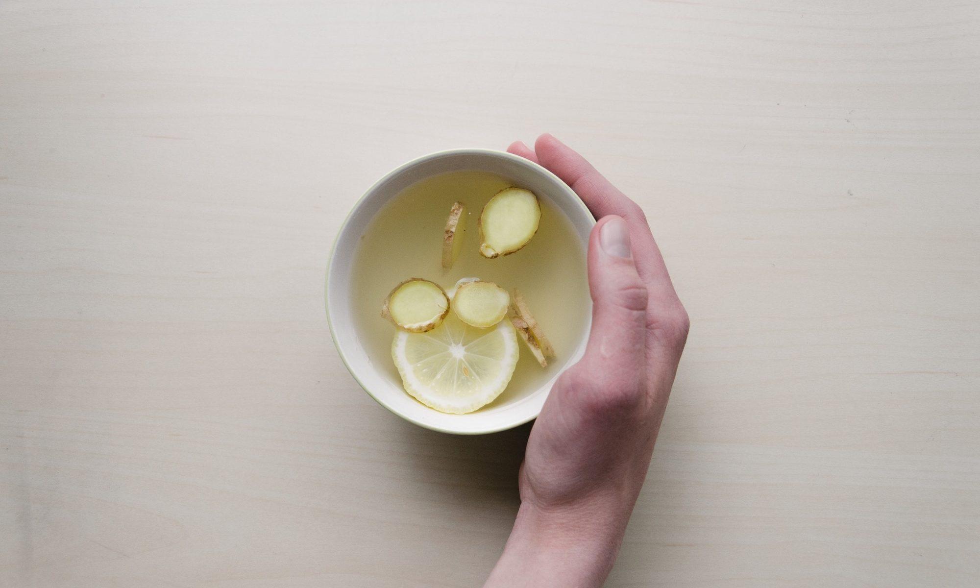 Draufsicht auf eine Tasse mit einer klaren Flüssigkeit, in der Ingwerstücke schwimmen und die von einer Hand gehalten wird.