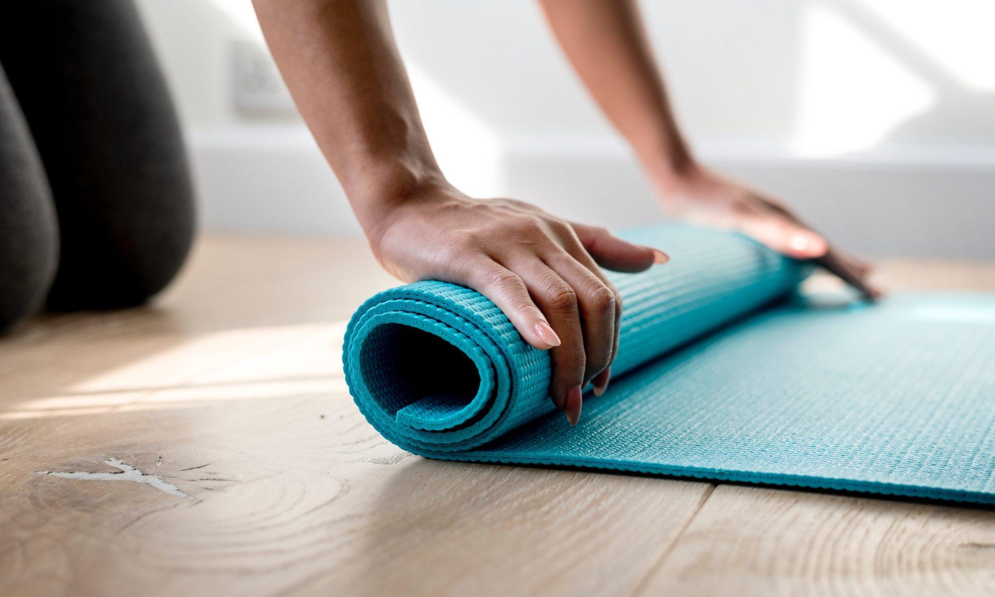 Closeup von Händen mit langen Fingernägeln, die eine türkisfarbene Yogamatte ausrollen.