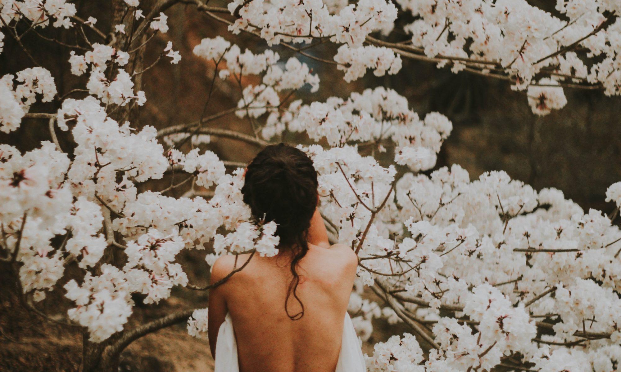 Rückansicht einer nackten Person mit langen schwarzen Haaren vor einer weiß blühenden Hecke.