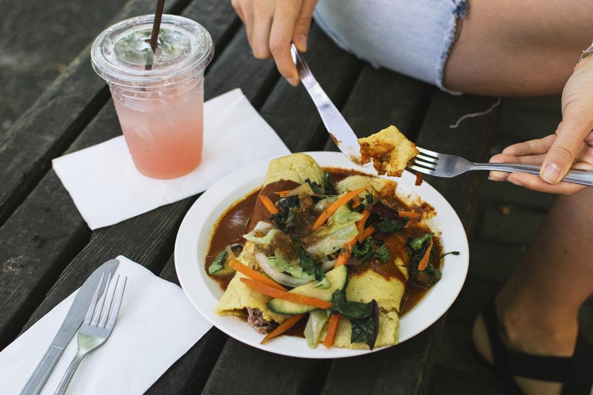 Enchiladas auf einem Teller, daneben ein rosa Getränk in einem Plastikbecher mit Strohhalm.