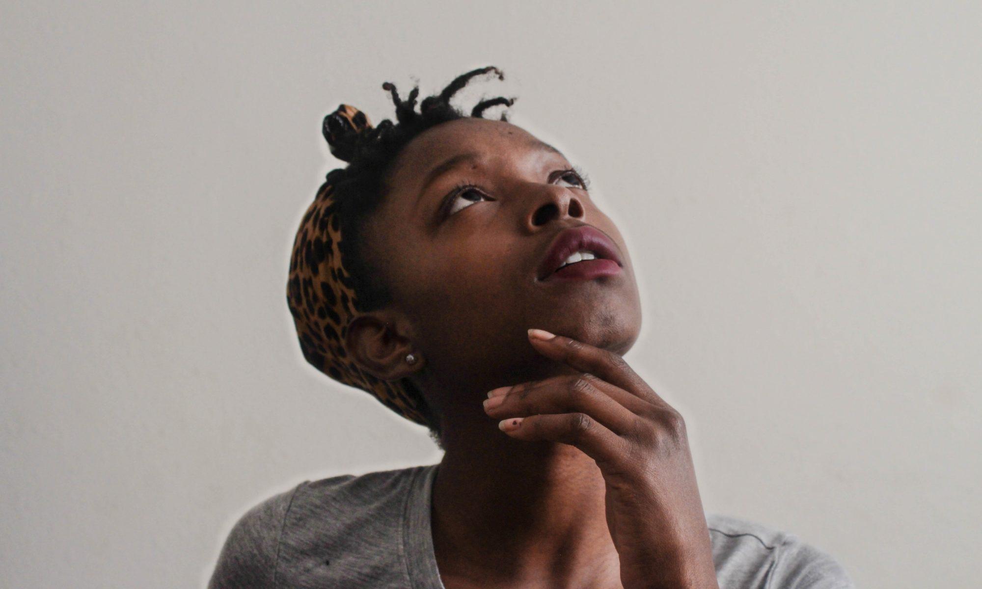 Porträt einer Frau in grauem T-Shirt, die nachdenklich nach oben blickt und sich eine Hand ans Kinn hält