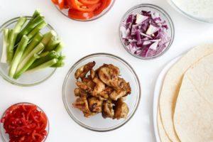 Wrap-Zutaten in Glasschüsseln (Frühlingszwiebeln, gegrilltes Fleisch, rote Zwiebeln, Paprika, Tomatenstücke) sowie Tortillas auf einem Teller.